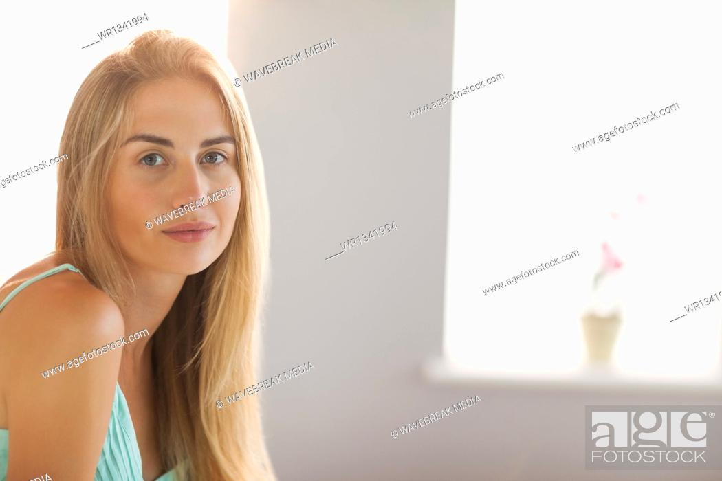 Stock Photo: Smiling blonde woman sitting on her bed.