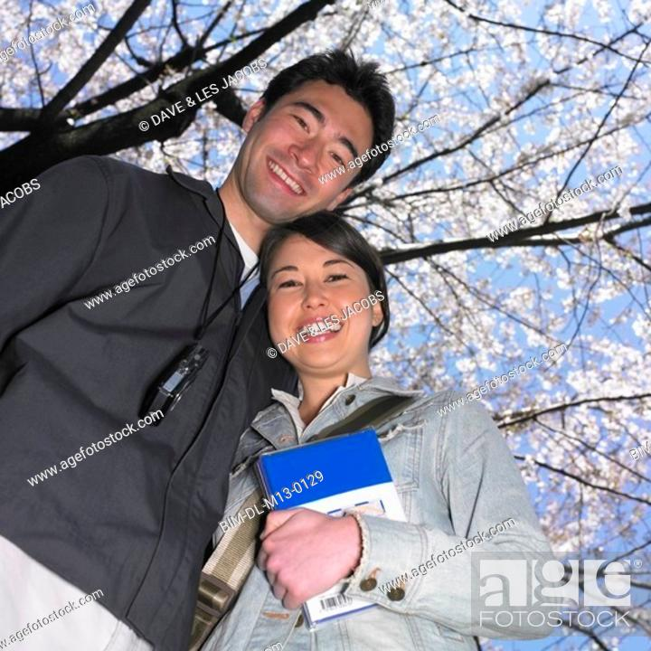 Stock Photo: Low angle view of Asian couple with guide book.