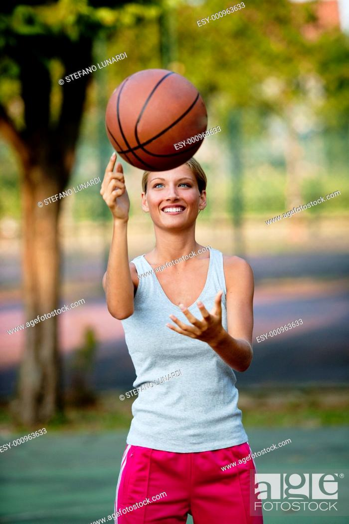 Stock Photo: Young athlete spinning basketball.