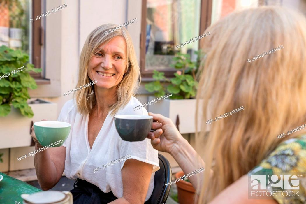 Imagen: Female friends having coffee in outdoor cafe.