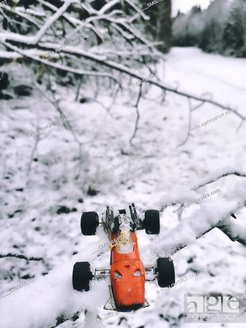 Stock Photo: 1970's red metal miniature toy racing car and driver on snow covered tree branch in snowy landscape, Sweden.
