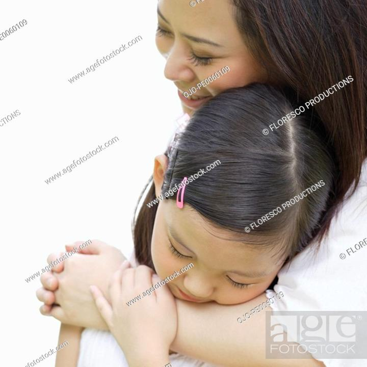 Stock Photo: Woman and young girl embracing indoors.