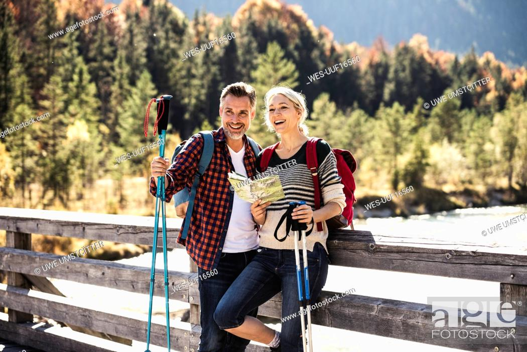 Stock Photo: Austria, Alps, happy couple on a hiking trip with map on a bridge.