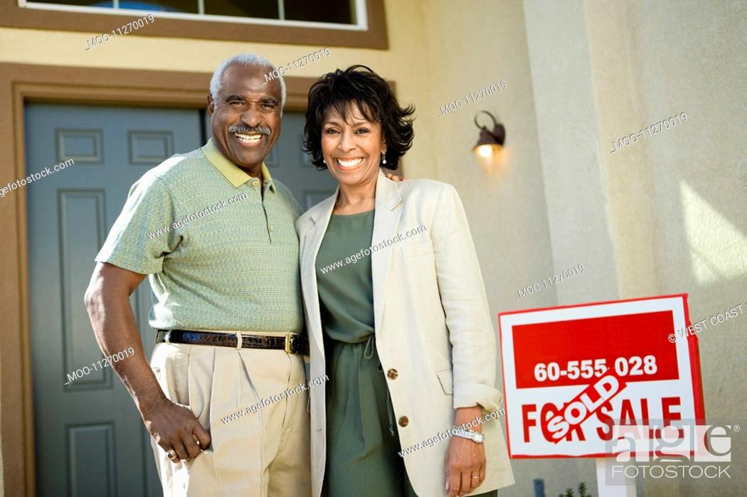 Stock Photo: Middle-aged couple standing in front of new home portrait.