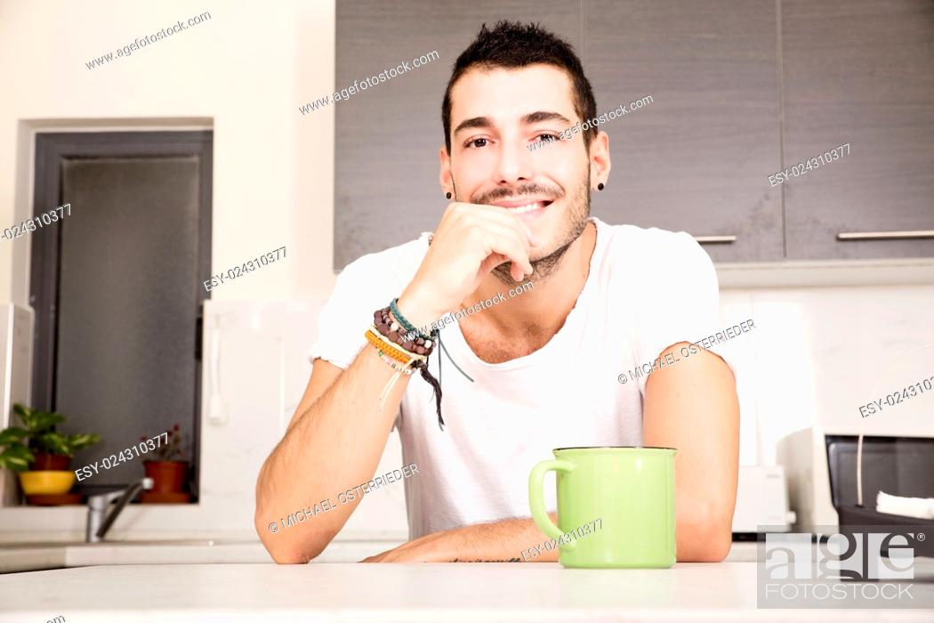 Imagen: A young man sitting in the kitchen and drinking coffee.