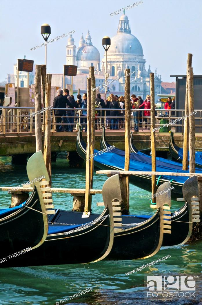 Stock Photo: Gondolas, in the foreground and tourists in front of Salute Church, in the background, Venice, Italy.