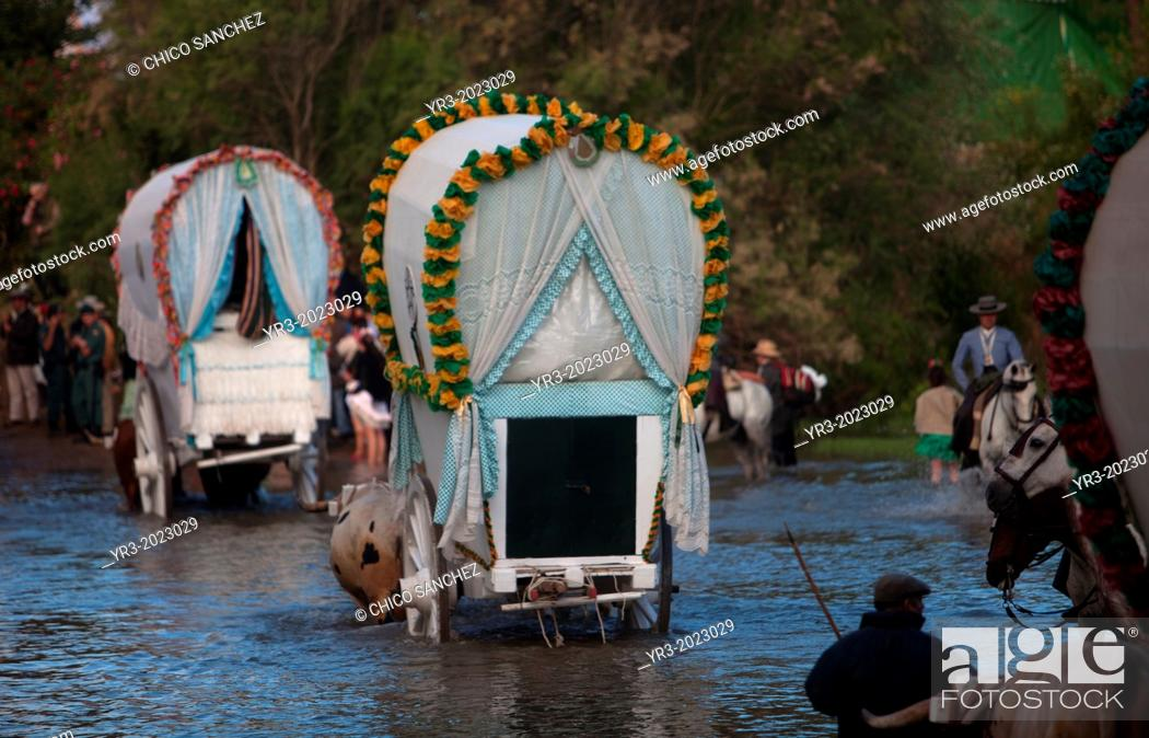 Stock Photo: Riders and oxcarts of the Triana Brotherhood cross the Guadiamar's river ford, known as Vado del Quema, during the pilgrimage to the shrine of the Virgin of.