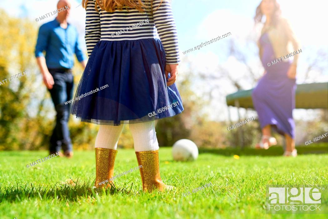 Stock Photo: Low section of girl in garden with family playing with football.