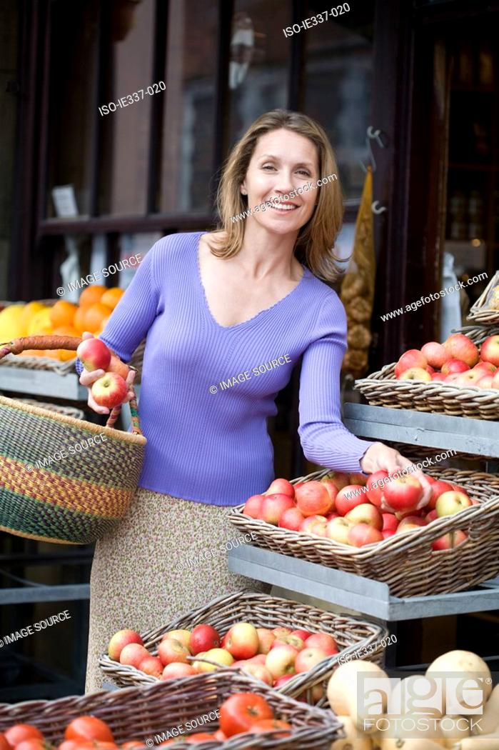 Stock Photo: Woman buying apples.