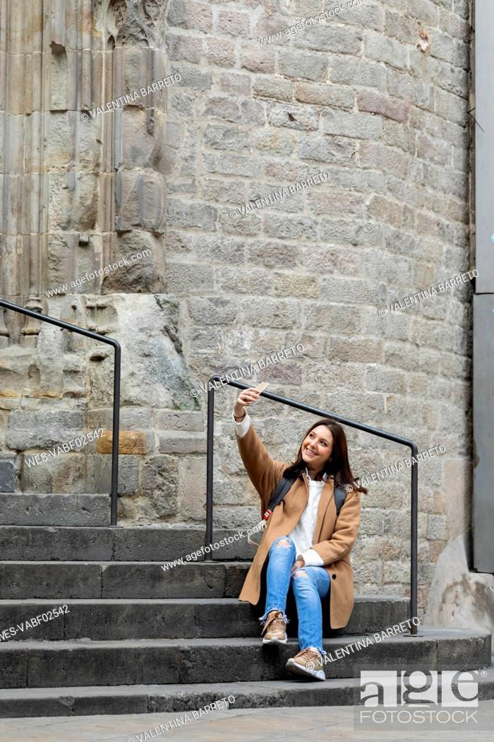 Imagen: Smiling young woman sitting on stairs in the city taking a selfie, Barcelona, Spain.