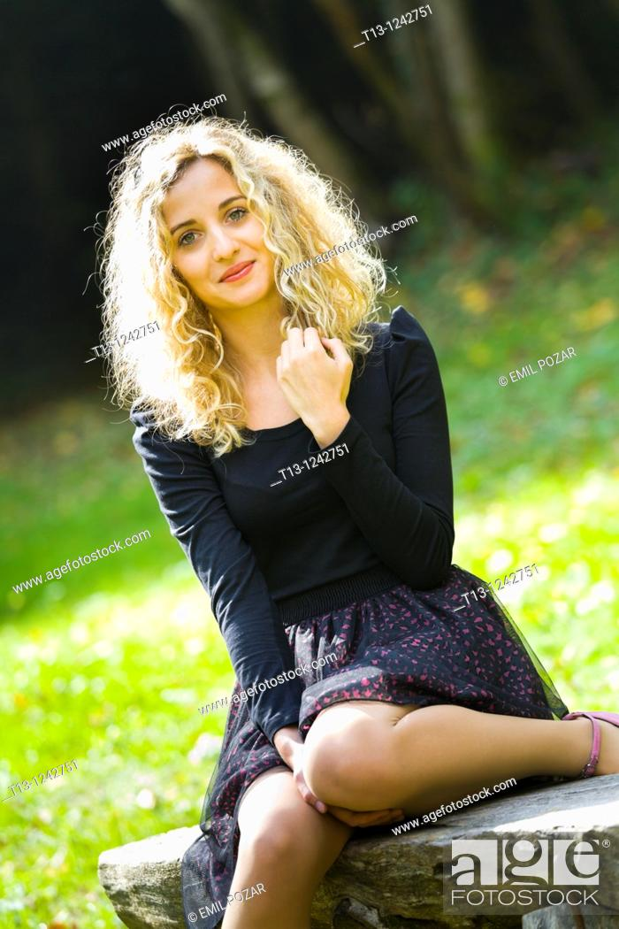 Stock Photo: Young woman with a curly hair is sitting in the park.