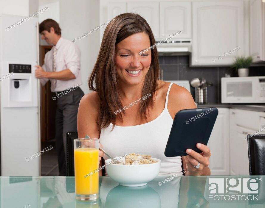 Stock Photo: USA, Illinois, Metamora, young woman having breakfast cereal and holding digital tablet.