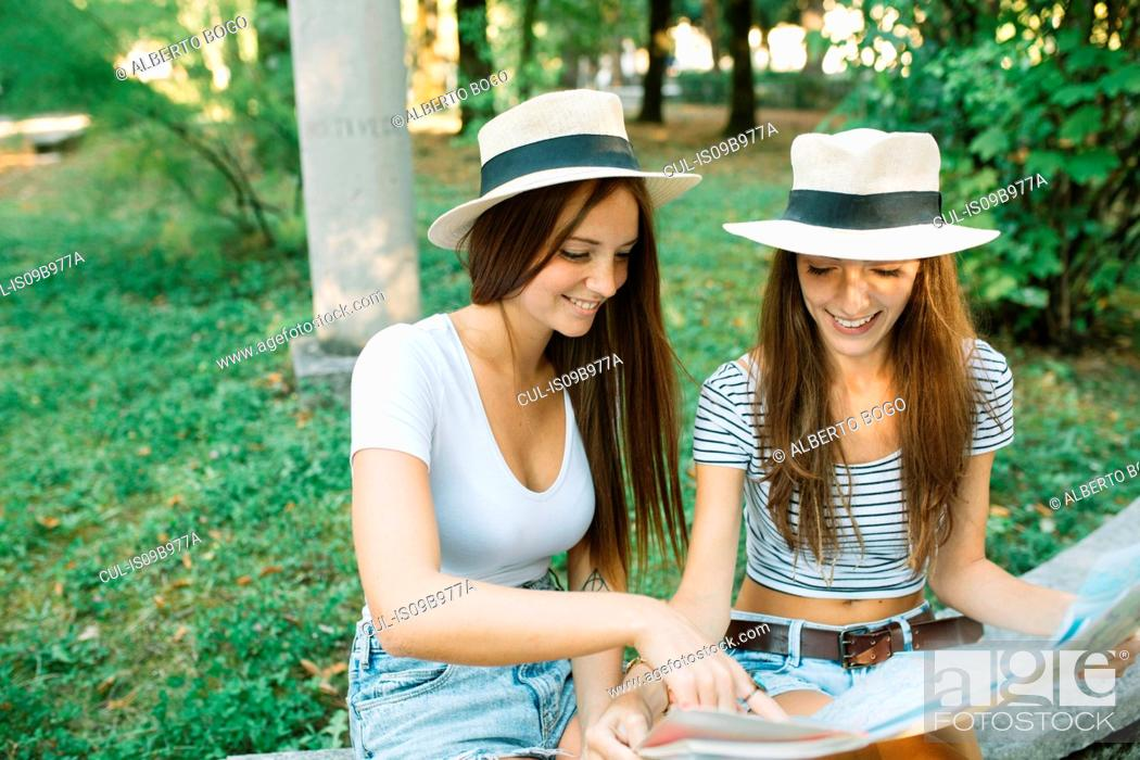 Stock Photo: Two young female friends sitting on bench pointing at map in park.