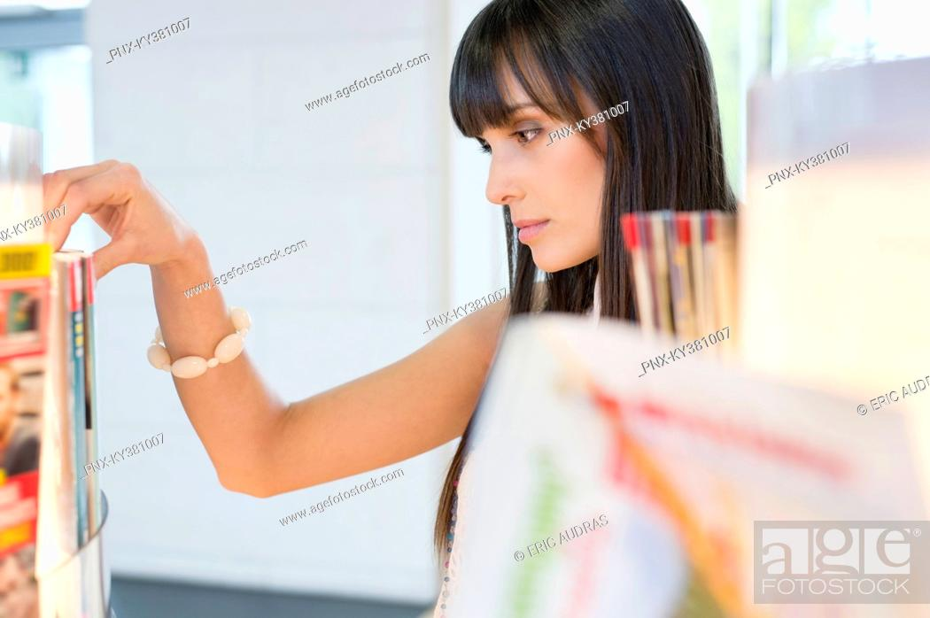 Stock Photo: Close-up of a woman choosing magazine from a bookshelf.
