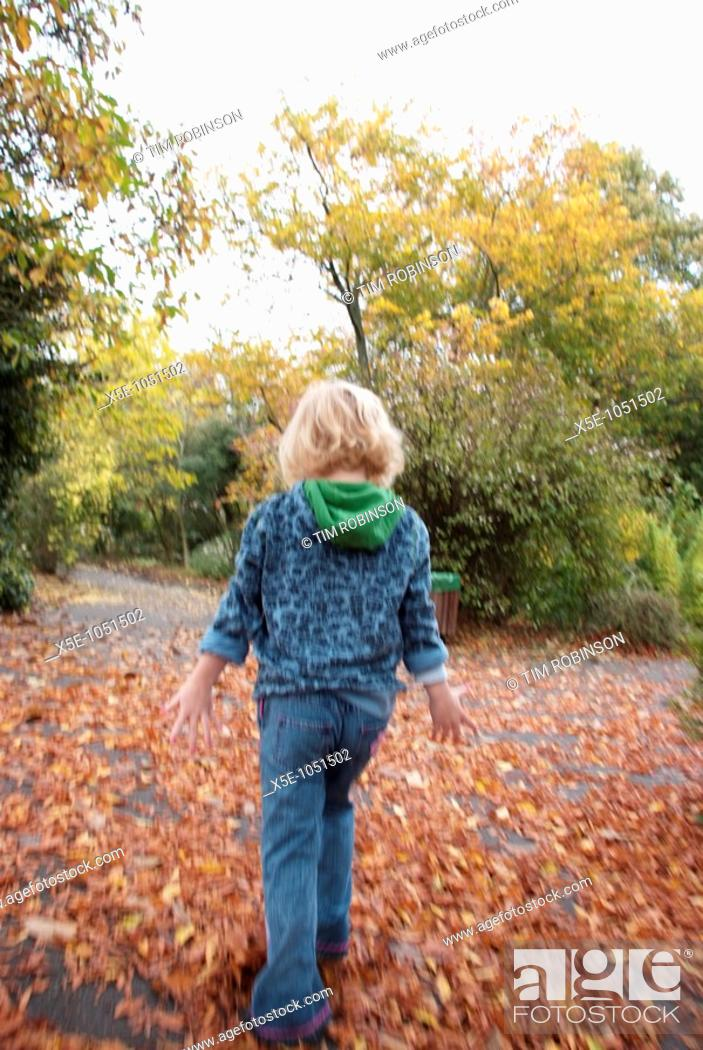 Stock Photo: Rearview 6 year girl walking away down path in park.