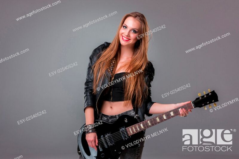 Stock Photo: Beautiful girl with long hair playing guitar in rock style on a gray background.