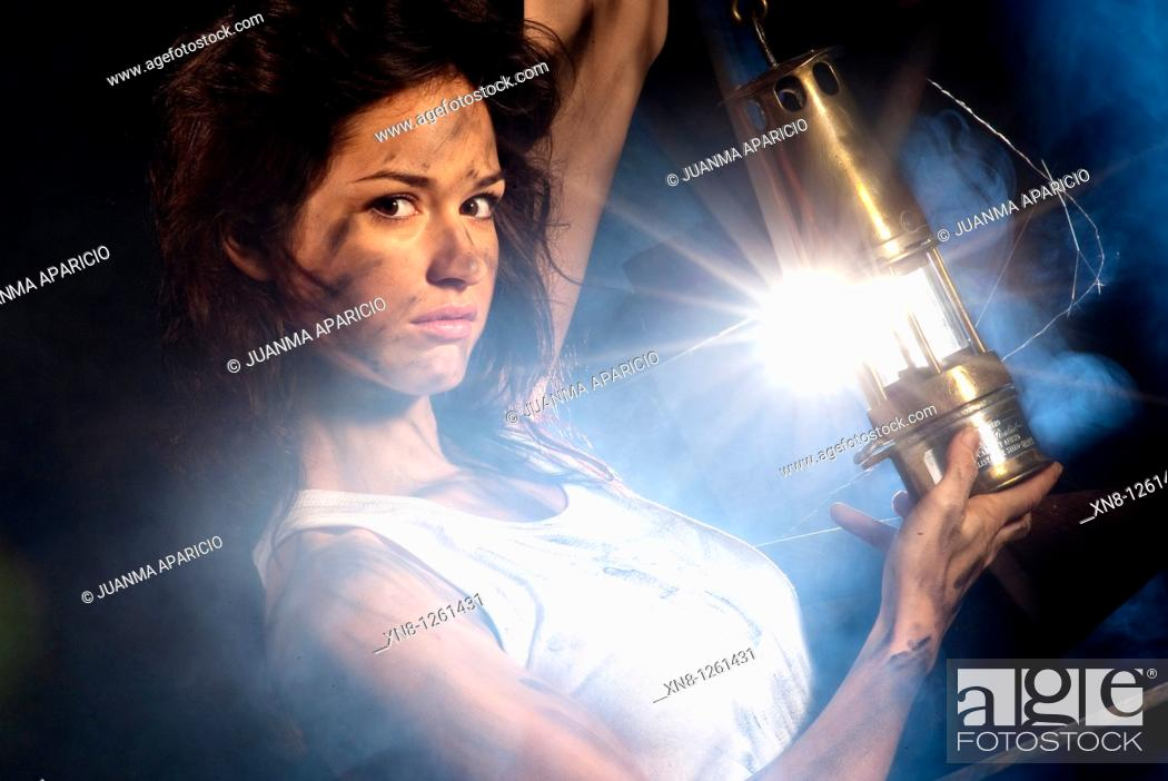 Stock Photo: Portrait of young woman wiht miner's lamp representing the work inside a mine.