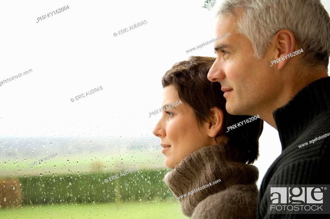 Stock Photo: Mature man and a mid adult woman looking out through a window.