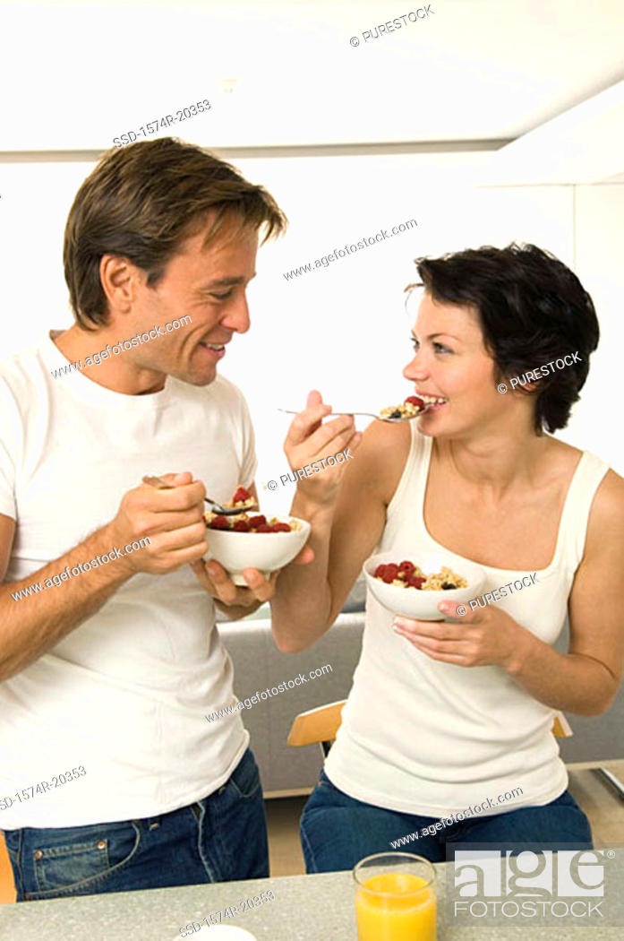 Stock Photo: Close-up of a young couple holding bowls of fruit salad and smiling.