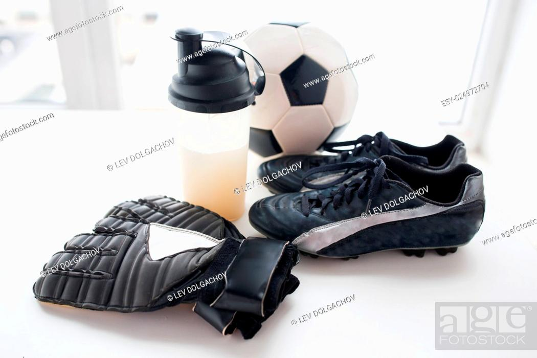 Imagen: sport, football and sports equipment concept - close up of soccer ball, boots, goalkeeper gloves and protein shake bottle with drink.