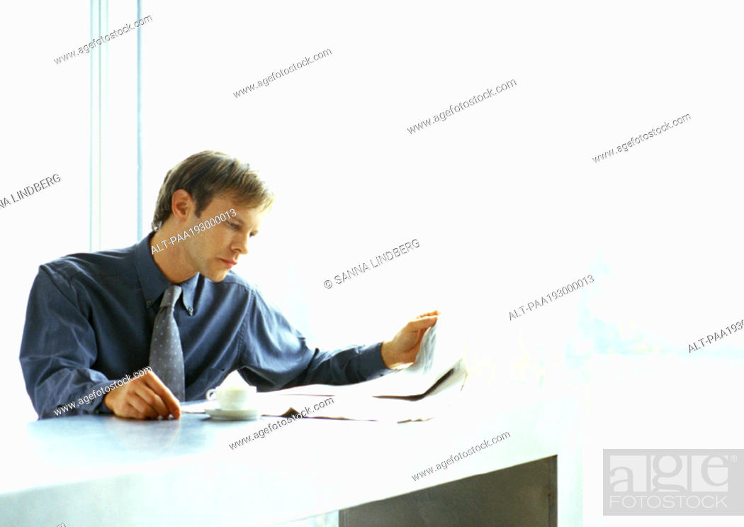Stock Photo: Businessman reading newspaper and drinking coffee.