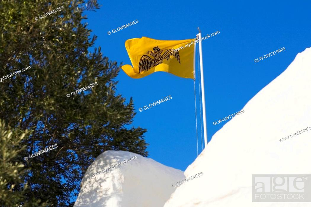Stock Photo: Low angle view of a flag over a monastery, Monastery of the Apocalypse, Patmos, Dodecanese Islands, Greece.