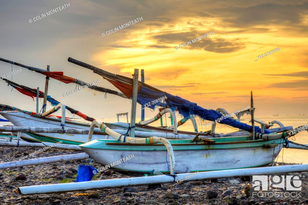 Stock Photo: Fishing boats with outriggers at sunset, Bali, Indonesia.