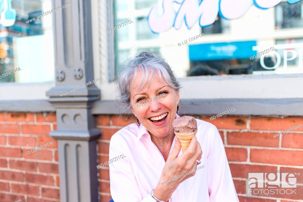 Stock Photo: Senior woman sitting on sidewalk with chocolate ice cream cone, portrait.