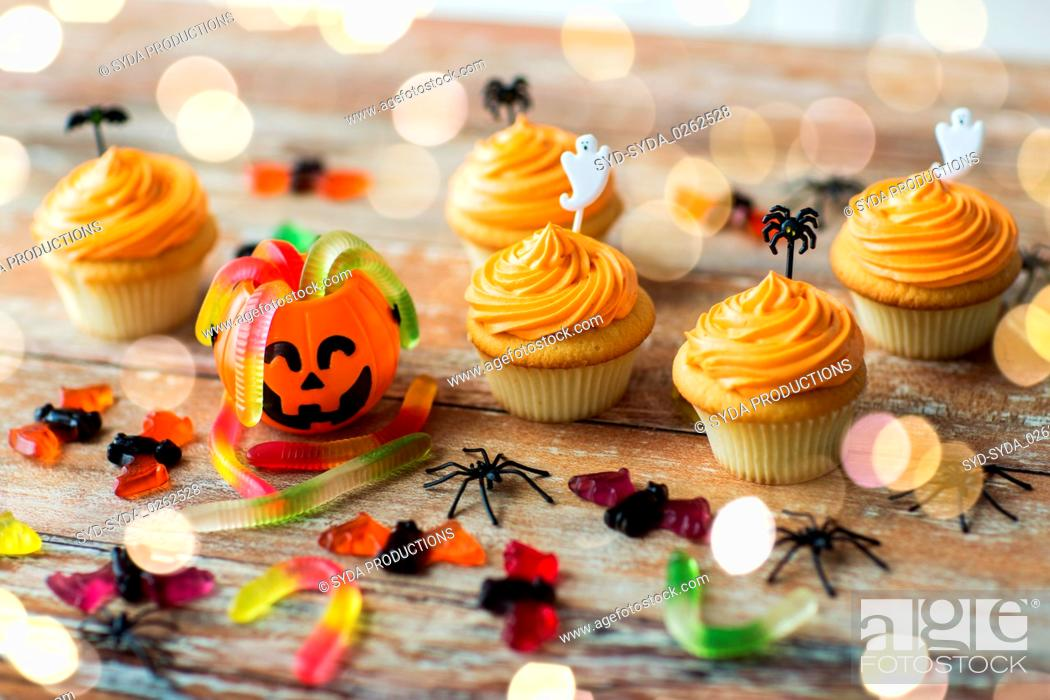 Stock Photo: halloween party decorated cupcakes on wooden table.
