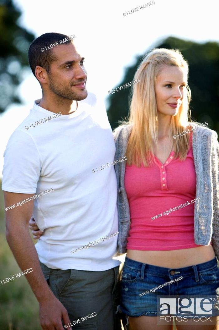 Stock Photo: A young couple standing outdoors, smiling.