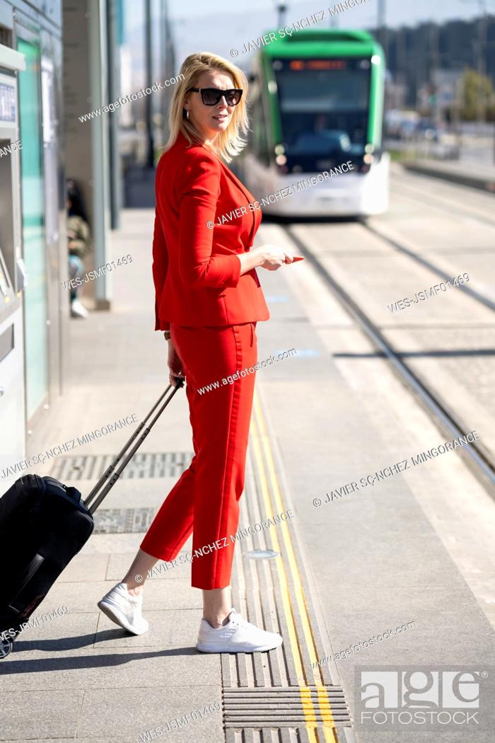 Stock Photo: Blond businesswoman wearing red suit, waiting for the next train.