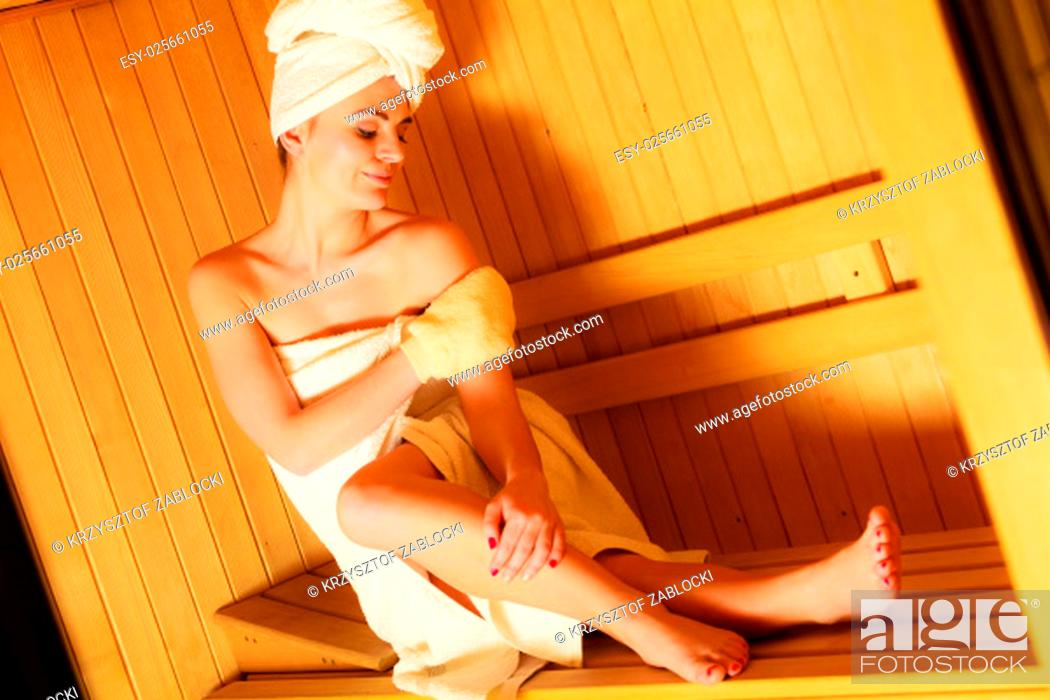 Stock Photo: spa beauty treatment and relaxation concept. woman white towel relaxing in wooden sauna room, making massage with exfoliation glove.