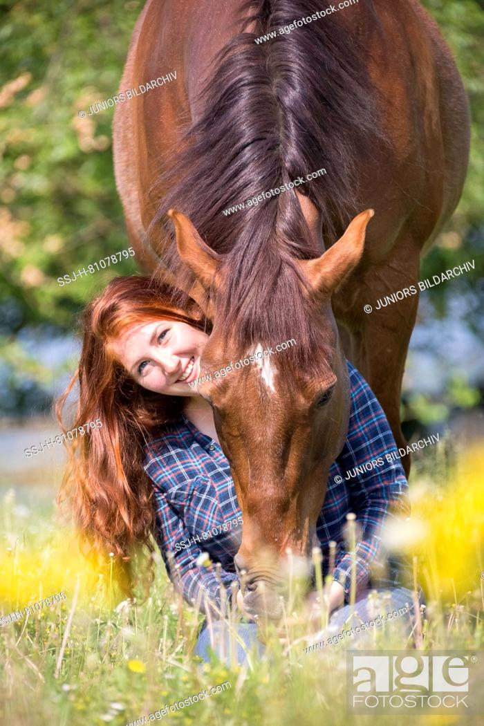 Stock Photo: Missouri Fox Trotter. Red-haired young woman with chestnut gelding on a pasture. smooching. Switzerland.