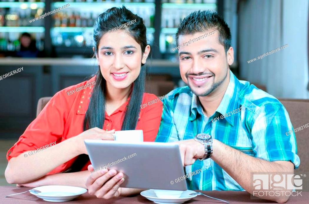 Stock Photo: Asian woman and man are sitting in a bar or cafe and are surfing the internet with a tablet computer.