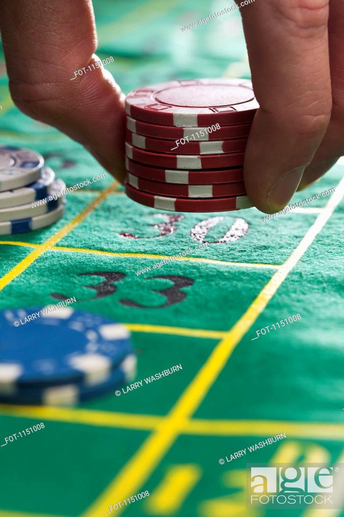 Stock Photo: A man placing gambling chips on number 30, detail of fingers.