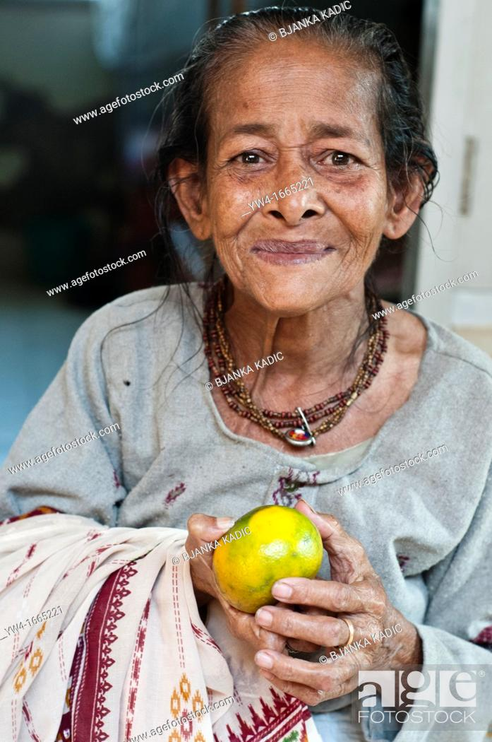 Stock Photo: Widow with an orange in her hands, Ma Dham Ashram, run by NGO Guild of Service, Vrindavan, Uttar Pradesh, India.