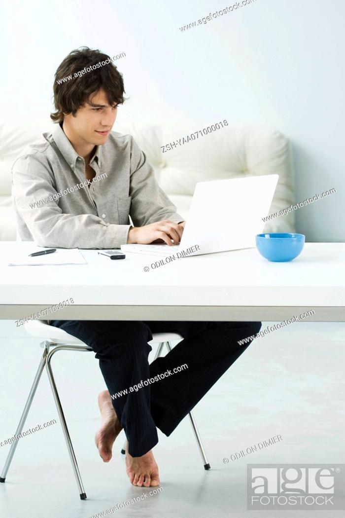 Stock Photo: Man sitting at table, using laptop computer.
