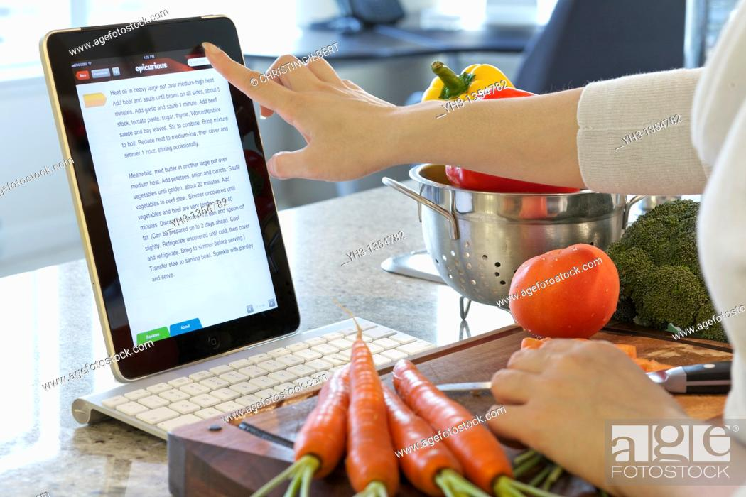Stock Photo: Woman browsing cooking instruction online with Epicurious iPad cooking app.