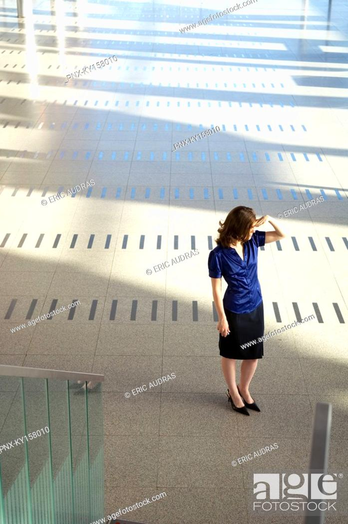 Stock Photo: High angle view of a businesswoman shielding her eyes.