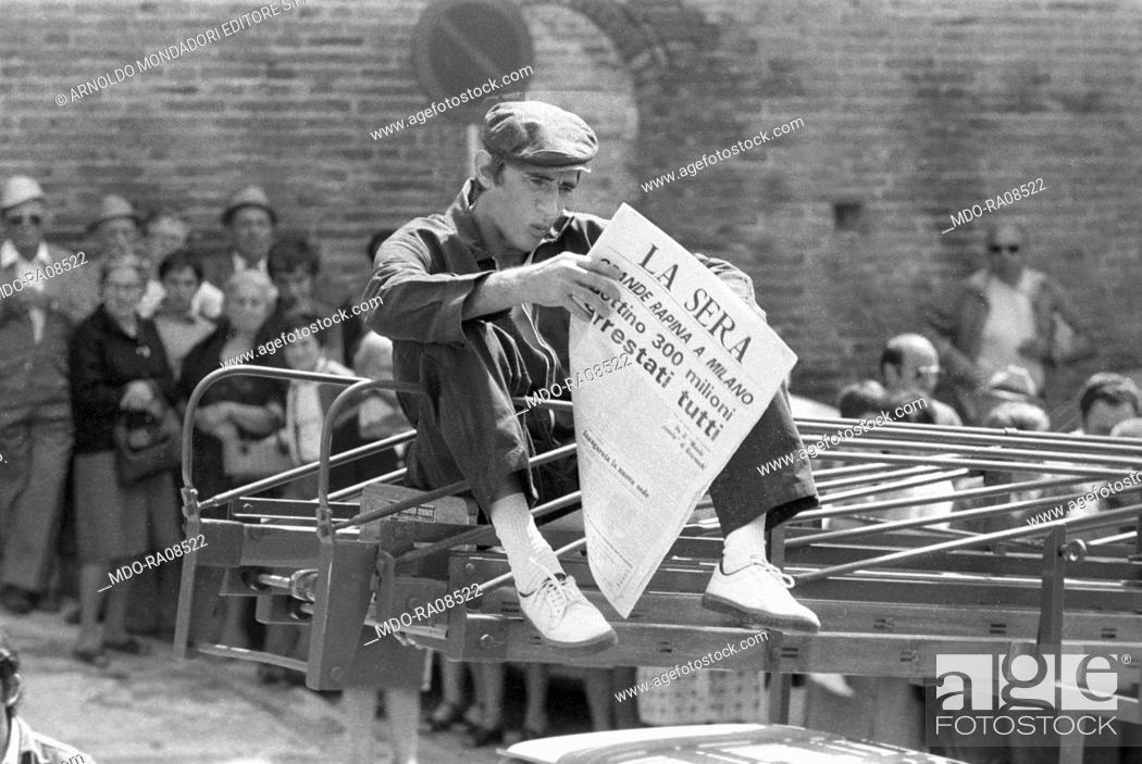Photo de stock: Italian actor Walter Chiari (Walter Annichiarico) reading a newspaper in the film Passi furtivi in una notte boia. 1976.