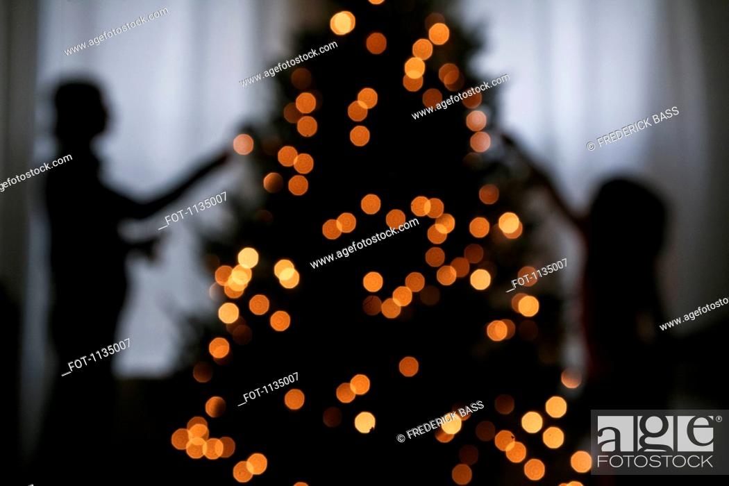 Stock Photo: Silhouette of mother and daughter decorating a Christmas tree.