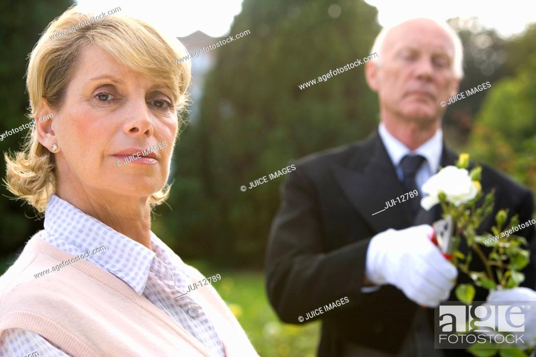 Stock Photo: Portrait of mature woman, butler pruning bush in background.