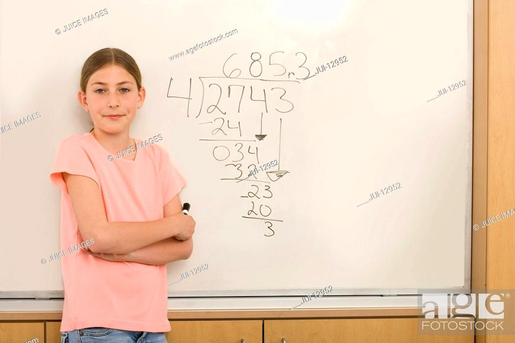 Stock Photo: Girl 10-12 by equation on whiteboard in classroom, portrait.