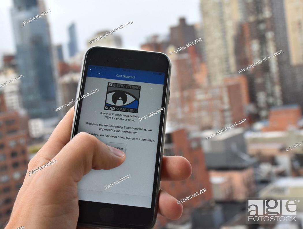 Stock Photo: A user holds a smart phone in his hand which displays the terrorism alert app 'See something, say something' on the Upper East Side in New York, USA.