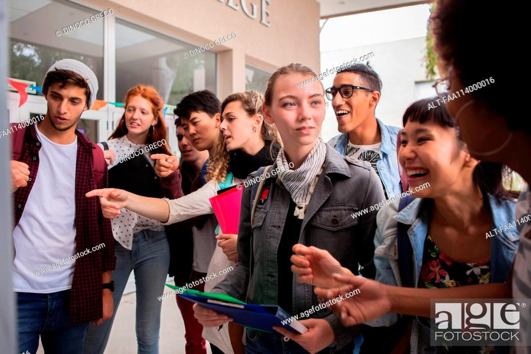 Stock Photo: College students looking at information posted on campus.