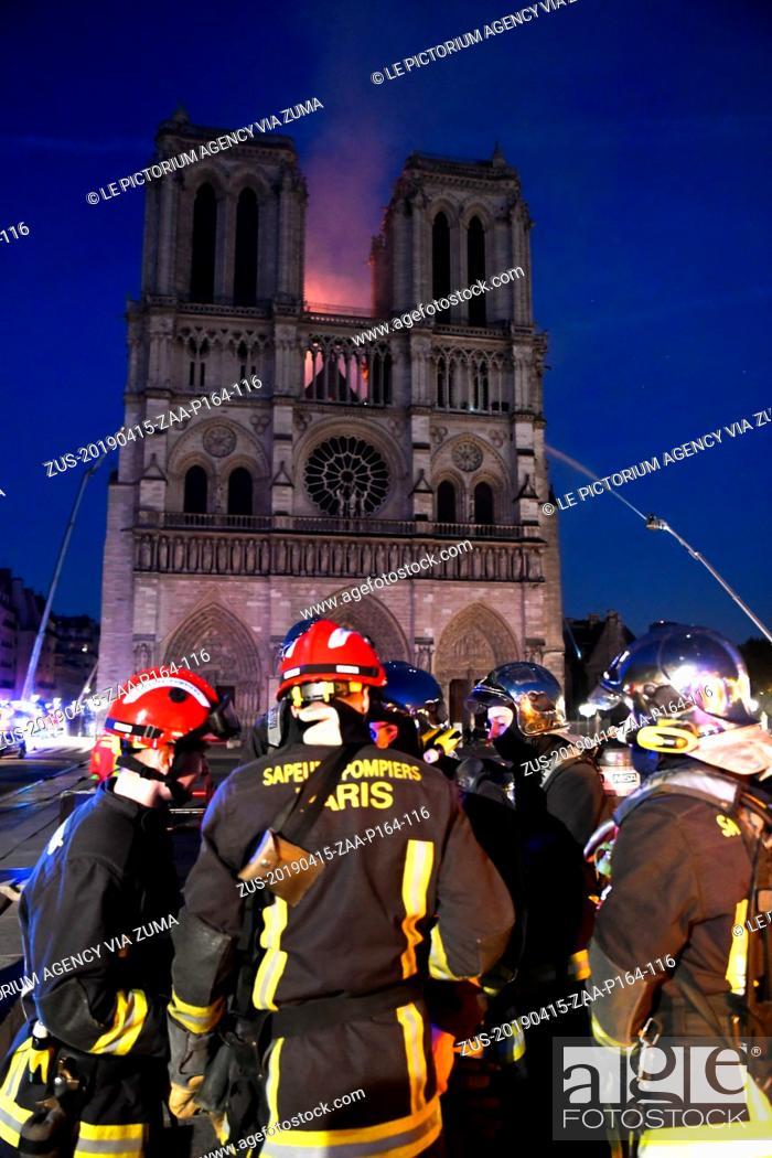 Stock Photo: April 15, 2019 - Paris, Paris, France - firefighters at the doors of Notre Dame de Paris Cathedral during the fire on April 16, 2019.
