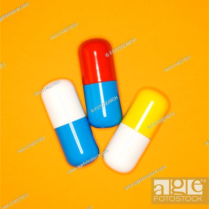 Stock Photo: Medical pills on a orange background.