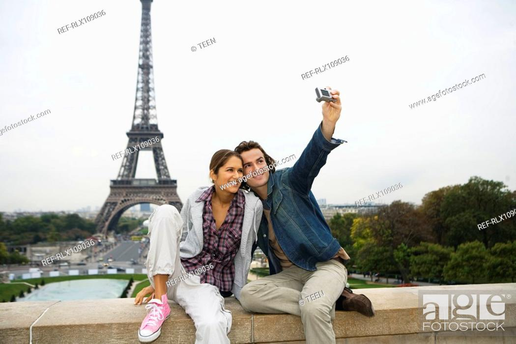 Stock Photo: Young couple sitting on wall, man taking photo, Eiffel tower in background.