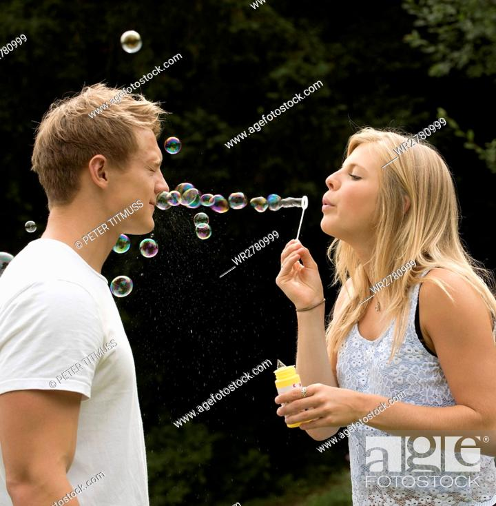Stock Photo: Teenage girl blowing bubbles at her boyfriend.