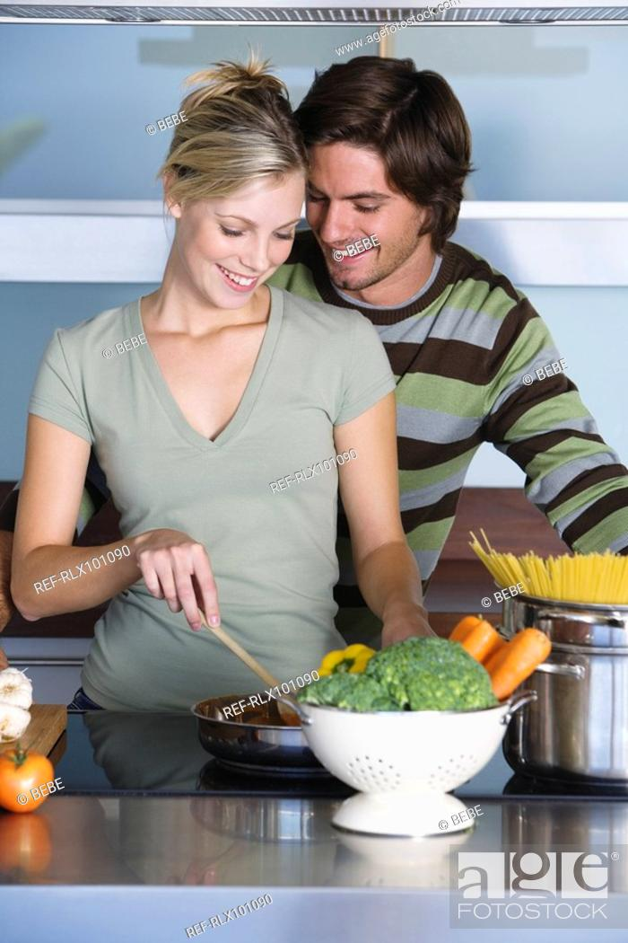 Stock Photo: Young couple in modern kitchen, cooking together, hugging, smiling.